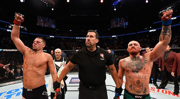 Conor McGregor of Ireland and Nate Diaz raise their hands and wait to hear the judges decision after their welterweight bout during the UFC 202 event at T-Mobile Arena on August 20, 2016 in Las Vegas, Nevada. (Photo by Josh Hedges/Zuffa LLC/Zuffa LLC via Getty Images)