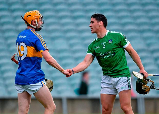 Limerick's Sean Finn shakes hands with Tipperary's Cian Darcy. Photo: Ramsey Cardy/Sportsfile