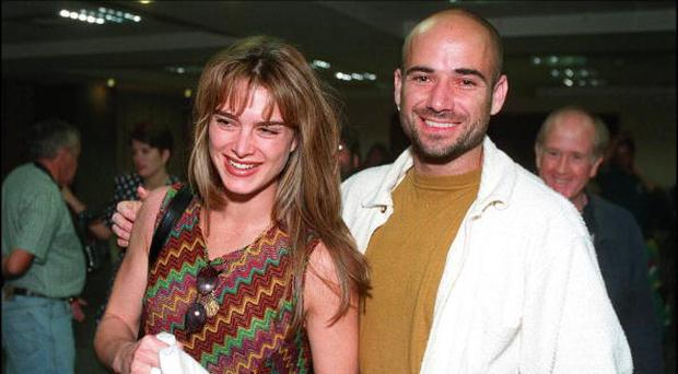 US tennis star Andre Agassi (R) arrives with his girlfriend Brooke Shields at Johannesburg International airport 07 December. (Photo credit should read TREVOR SAMSON/AFP/Getty Images)