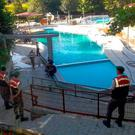 Paramilitary police officers investigate after five people were caught up in an electrical current in the pool at the park in the town of Akyazi, in Sakarya province ( IHA via AP)
