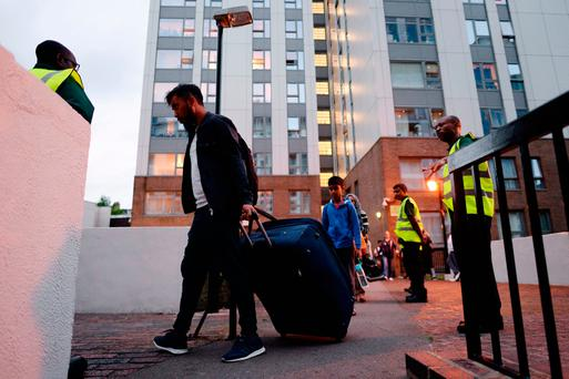 Residents leave the Taplow tower block on the Chalcots Estate in Camden, London, as the building is evacuated in the wake of the Grenfell Tower fire to allow