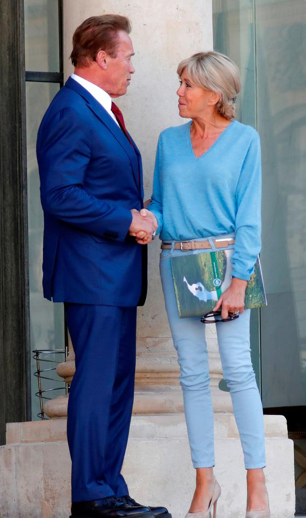 Former California Governor Arnold Schwarzenegger (L) speaks with Brigitte Macron, wife of French President Emmanuel Macron as he leaves the Elysee Palace in Paris, France, June 23, 2017. REUTERS/Charles Platiau