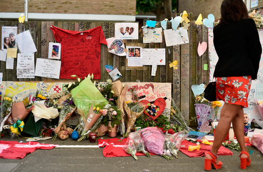 Solidarity: A woman looks at flowers, tributes and messages left for the victims of the Grenfell Tower fire in west London. Photo: Hannah McKay/Reuters