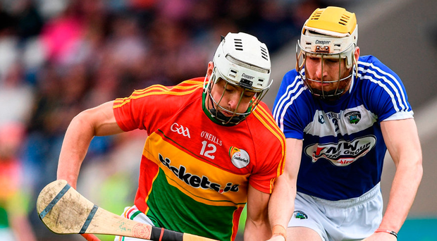 Carlow's James Doyle in action against Leigh Bergin of Laoi. Photo: Ramsey Cardy/Sportsfile
