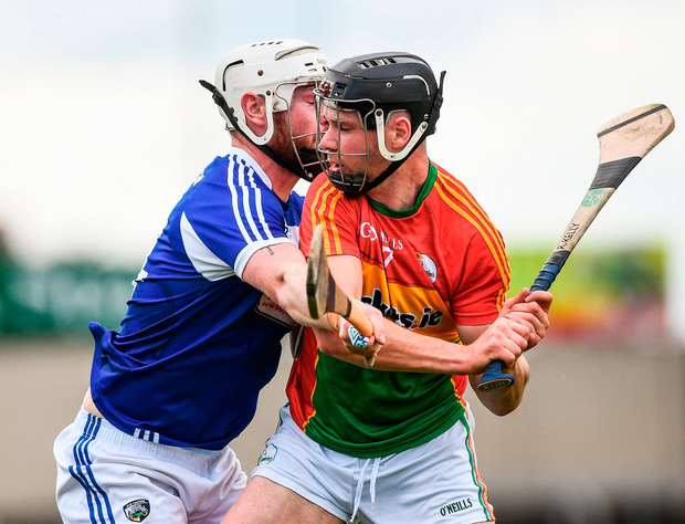Carlow's Richard Kelly is tackled by Neil Foyle of Laois. Photo: Ramsey Cardy/Sportsfile