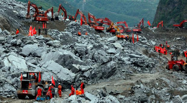 Heavy machinery is deployed to move debris during the search for victims at the site of a landslide in Maoxian County in southwestern China's Sichuan Province. Photo: AP