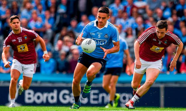 Dublin's Niall Scully goes on the attack with Westmeath's Mark McCallon in pursuit during yesterday's Leinster SFC semi-final at Croke Park. SPORTSFILE