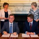 Britain's Conservative party leader and Prime Minister Theresa May (R) stands next to Democratic Unionist Party (DUP) leader Arlene Foster (L), as DUP MP Jeffrey Donaldson (2L) sits and signs paperwork with Britain's Parliamentary Secretary to the Treasury, and Chief Whip, Gavin Williamson, whilst posing for a photograph inside 10 Downing Street in central London on June 26, 2017. REUTERS/Daniel Leal-Olivas/Pool