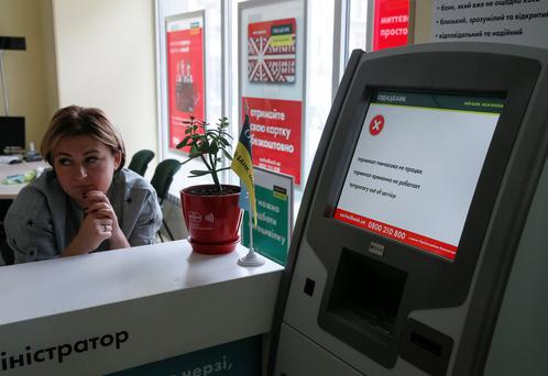 An employee sits next to a hacked payment terminal at a branch of Ukraine's state-owned bank Oschadbank. Picture: Reuters