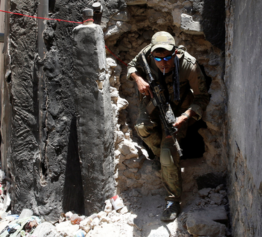An Iraqi soldier walks out of a hole in the Old City of Mosul. Photo: Reuters