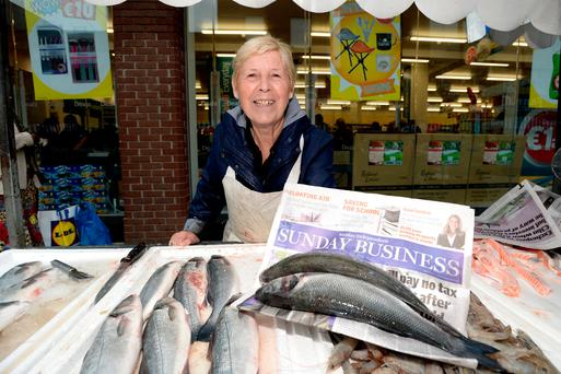 Fishmonger Margaret Buckley uses newspaper to wrap her stock on Moore Street, Dublin Photo: Justin Farrelly