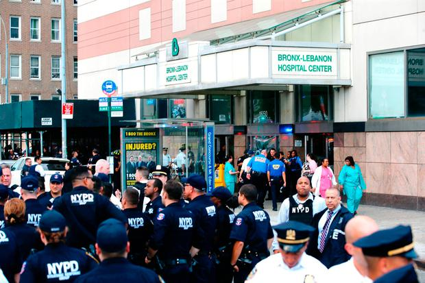 Patients and hospital staff walk past police outside the Bronx-Lebanon Hospital as they respond to an active shooter north of Manhattan in New York on June 30, 2017. / AFP PHOTO / EDUARDO MUNOZ ALVAREZEDUARDO MUNOZ ALVAREZ/AFP/Getty Images
