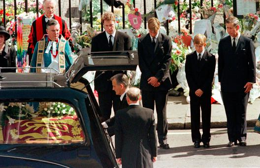 Earl Spencer, Prince William, Prince Harry and Prince Charles watch as the coffin of Diana, Princess of Wales is placed into a hearse at Westminster Abbey following her funeral service, London, Britain September 6, 1997. REUTERS/Kieran Doherty/File Photo