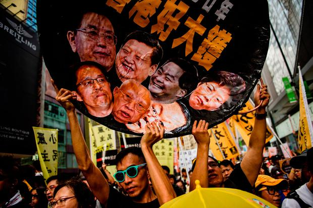 Something's cooking: A protester in Hong Kong holds a wok-shaped artwork with pictures showing the faces of Chinese politicians including Chinese president Xi Jinping. Photo: AFP/Getty