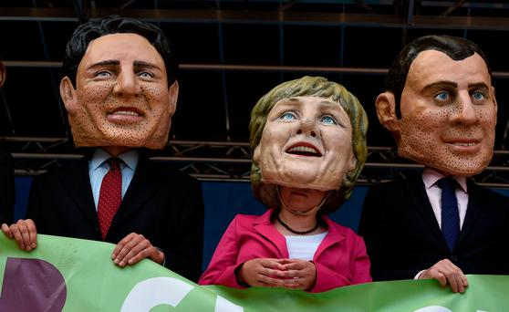 Demonstrators against the G20 Summit stand on stage wearing masks depicting German Chancellor Angela Merkel, center, French President Emmanuel Macron, right, and Canadian Prime Minister Justin Trudeau, left, in Hamburg, Germany. Photo: AP