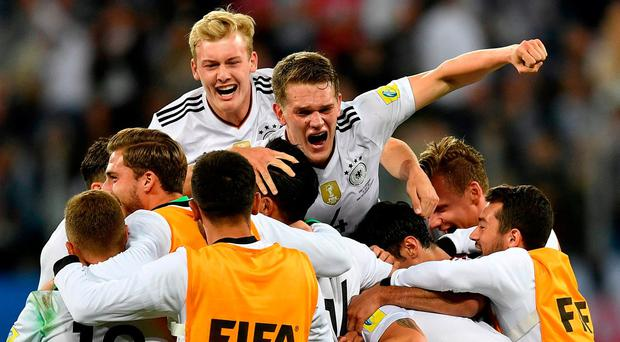 The German team celebrate with Julian Brandt, top left, and Matthias Ginter, top right, after winning the the Confederations Cup final soccer match between Chile and Germany, at the St.Petersburg Stadium, Russia