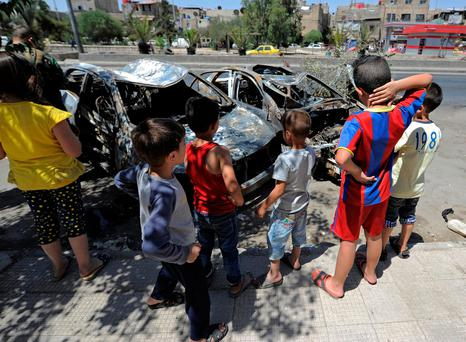 Children look at the wreckage of vehicles after the suicide bomb near the old city of Damascus. REUTERS/Omar Sanadiki