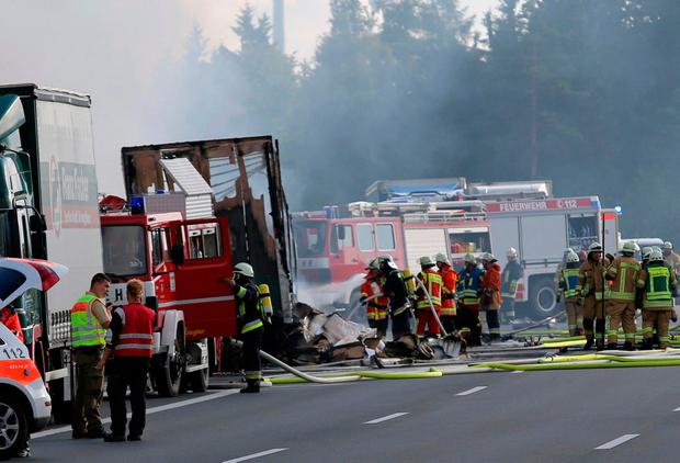 Rescue workers stand beside burnt-out coach on the motorway A9 near Muenchberg, southeastern Germany, Monday, July 3, 2017 after a bus crashed into a truck and caught fire. . (News5 / Fricke/NEWS5/dpa via AP)