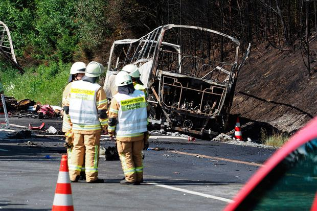 Fire fighters stand beside a burnt-out coach on the motorway A9 near Muenchberg, southeastern Germany, Monday, July 3, 2017 after a bus crashed into a truck and caught fire. (Nicolas Armer/dpa via AP)