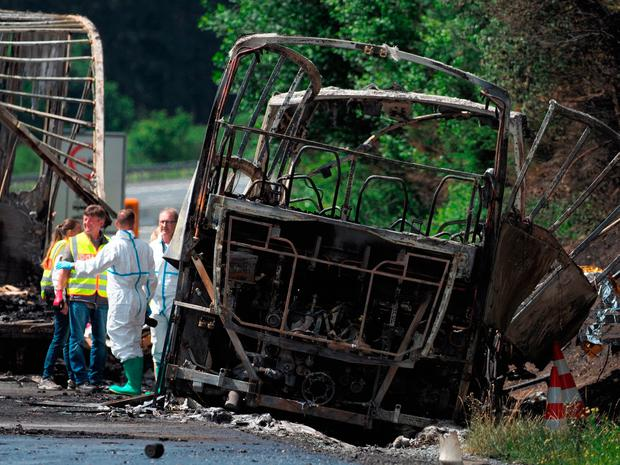 Fire fighters and rescuers stand beside a burnt-out coach on the motorway A9 near Muenchberg, southeastern Germany, Monday, July 3, 2017 after a bus crashed into a truck and caught fire. (Nicolas Armer/dpa via AP)