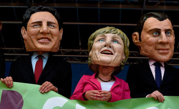 Demonstrators against the G20 Summit stand on stage wearing masks depicting German Chancellor Angela Merkel, center, French President Emmanuel Macron, right, and Canadian Prime Minister Justin Trudeau (Axel Heimken/dpa via AP)