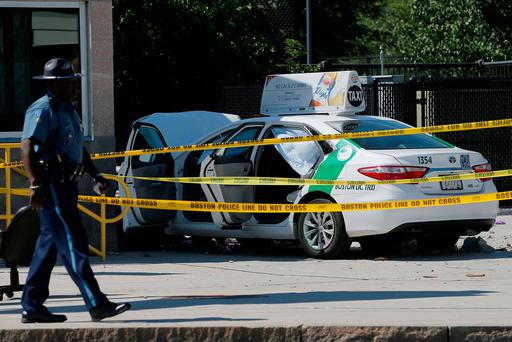 A Massachusetts State Police officer walks past the scene where a taxi cab crashed into a group of bystanders at the taxi pool at Logan International Airport in Boston (Reuters)