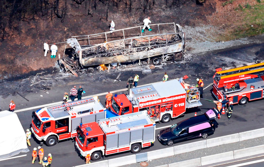 Fire and rescue workers stand near the burned-out wreckage of a passenger bus on the A9 highway in northern Bavaria. Photo: Getty images