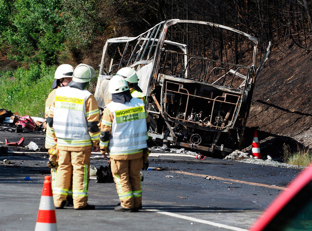 Fire fighters stand beside a burnt-out coach on the motorway A9 near Muenchberg, southeastern Germany, after a bus crashed into a truck and caught fire. Photo: AP