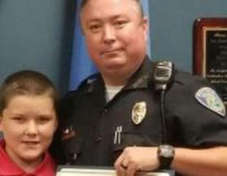 Officer Jody Thompson and his adopted son John (Image: KCCI News 8 via Independent News Service)