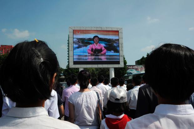 Pyongyang residents watch TV announcer Ri Chun-Hee speak about the successful launch of the intercontinental ballistic missile