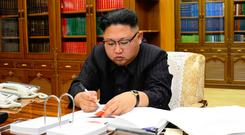 North Korean leader Kim Jong-Un signing the order to carry out the test-fire of the intercontinental ballistic missile Hwasong-14