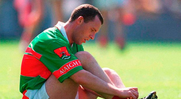 A dejected Kenneth Mortimer takes his boots off after Mayo's quarter-final defeat to Cork in 2002. Photo: Ray McManus / Sportsfile