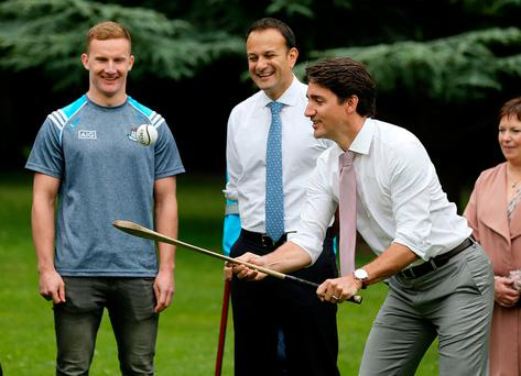 Dublin footballer Ciarán Kilkenny and Taoiseach Leo Varadkar watch Justin Trudeau solo a sliothar in Farmleigh Photo: Gerry Mooney