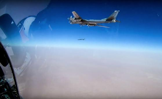 In this photo made from the footage taken from Russian Defense Ministry official web site on Wednesday, July 5, 2017 Russian strategic T-95 bomber launches X-101 cruise missiles on IS facilities in the area along the boundary between the provinces of Hama and Homs in Syria. The Russian military says its bombers have fired cruise missiles at the Islamic State group in Syria. (Russian Defense Ministry Press Service/ Photo via AP)