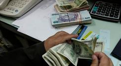 A currency exchange trader counts money at his office in Islamabad. Photo: Reuters