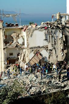 Rescuers work amid the rubble of a building that collapsed in Torre Annunziata, near Naples, southern Italy, Friday, July 7, 2017. A five-story apartment block collapsed early Friday near the southern Italian city of Naples, and authorities were digging by hand to find anyone who may have been trapped. (Ciro Fusco/ANSA via AP)