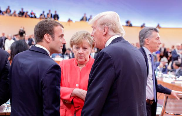 German Chancellor Angela Merkel talks to US President Donald Trump (R) and French President Emmanuel Macron at the start of the first working session of the G20 meeting in Hamburg, in Hamburg, Germany, July 7, 2017. REUTERS/Kay Nietfeld,Pool
