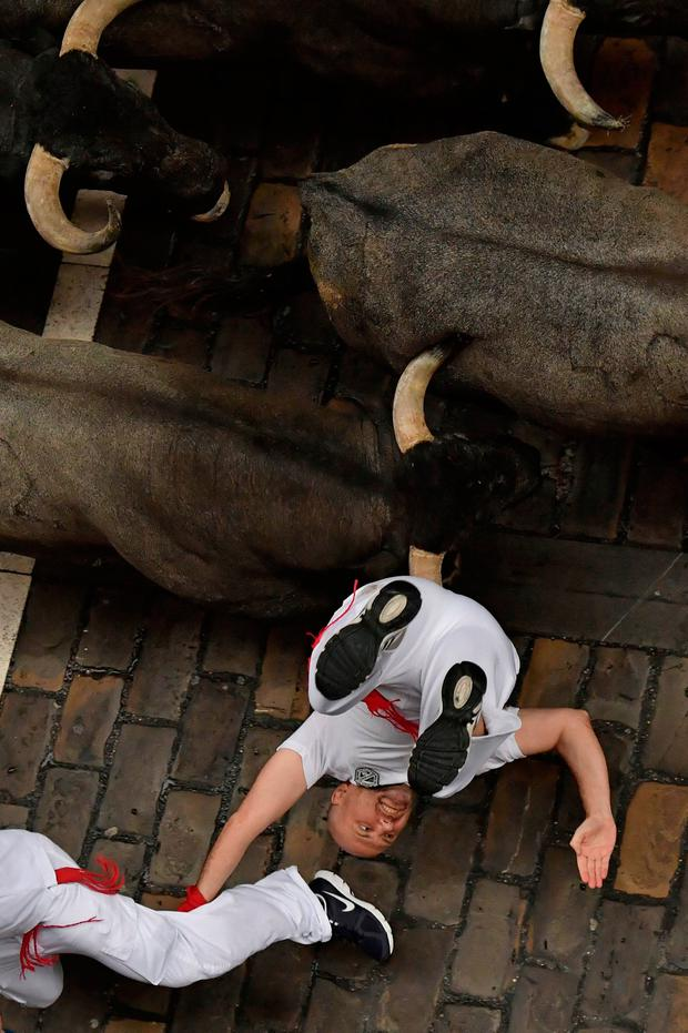 A revellers falls in front of Jose Escolar fighting bulls during the second running of the bulls at the San Fermin Festival, in Pamplona, northern Spain