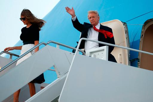 President Donald Trump waves as he and first lady Melania Trump arrive at Andrews Air Force Base, Saturday, July 8, 2017, in Andrews Air Force Base