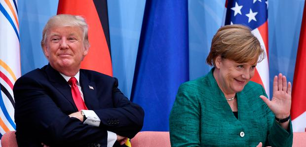 US President Donald Trump (L) and German Chancellor Angela Merkel attend the panel discussion
