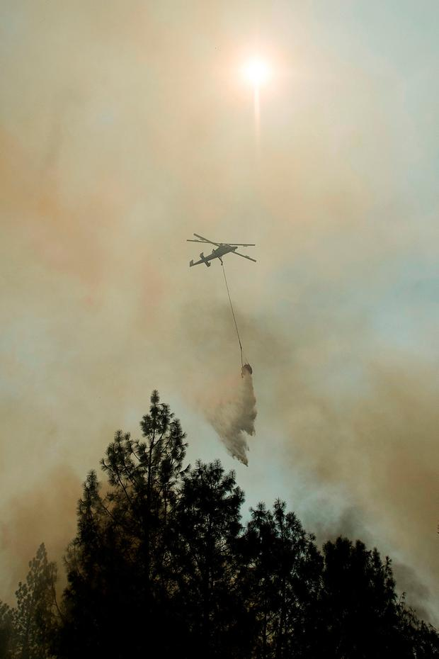 A helicopter drops water while battling a wildfire near Oroville, Calif., on Saturday (AP Photo/Noah Berger)
