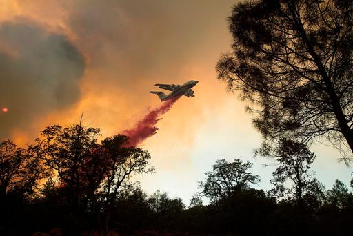 A plane drops retardant while battling a wildfire near Oroville, Calif., on Saturday (AP Photo/Noah Berger)