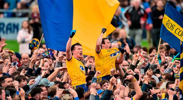 Tadgh O'Rourke and Niall Kilrory of Roscommon celebrate with supporters at the end of the game. Photo: David Maher/Sportsfile