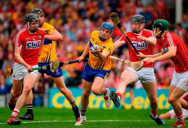 Clare's Shane O'Donnell passes under pressure from Cork players Darragh Fitzgibbon, 9, Damian Cahalane, 3, and Mark Coleman. Photo: Ray McManus/Sportsfile