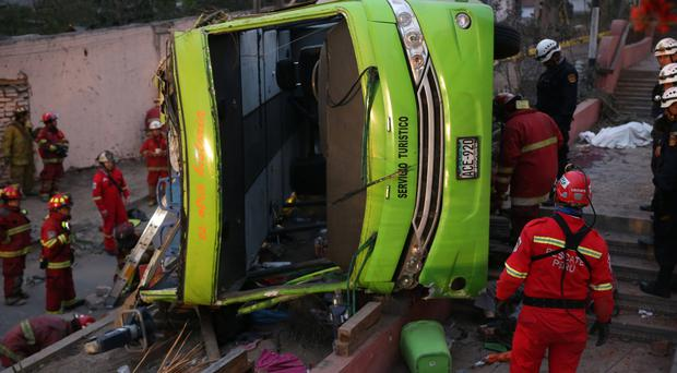Police officers, firemen and rescue personnel inspect a double-decker tourist bus after it crashed near the tourist site of San Cristobal in Lima