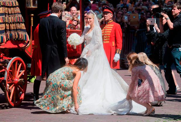Ekaterina of Hanover (C) is helped in a carriage next to her husband Prince Ernst August (L) after their church wedding ceremony in Hanover, central Germany, on July 8, 2017