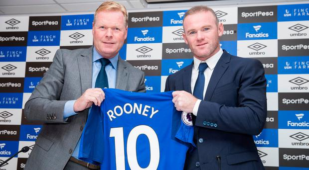 Wayne Rooney is given his shirt by Everton boss Ronald Koeman. Photo by Mark Robinson/Getty Images