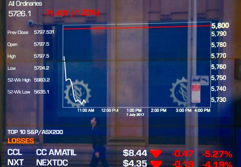 A pedestrian is reflected in a window displaying stock prices at the Australian Securities Exchange (ASX) in Sydney