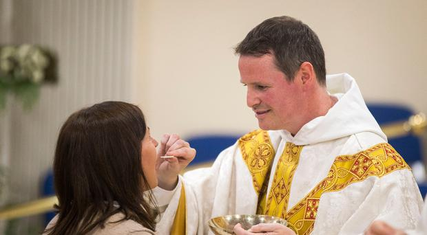 Former Manchester United player Philip Mulryne giving communion during his inaugural mass at St Oliver Plunkett Church in West Belfast following his ordination