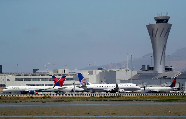 Departing and parked aircraft intersect at San Francisco International Airport, Tuesday, July 11, 2017, in San Francisco